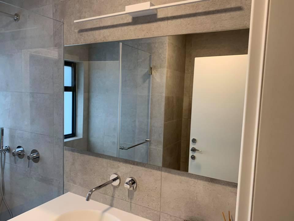 מראת זכוכית בחדר אמבטיה מעל כיור לבן, עם מקלחון זכוכית